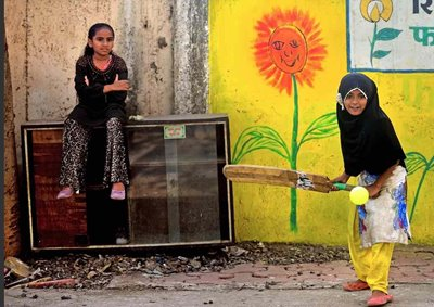 a Mumbai girl plays street cricket whilst her friend waits her turn to bat.